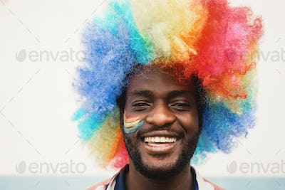 Happy young african man wearing lgbt rainbow flag wig - Focus on face