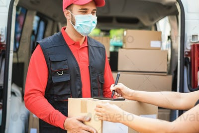 Young woman signing for shipping delivery box during coronavirus outbreak