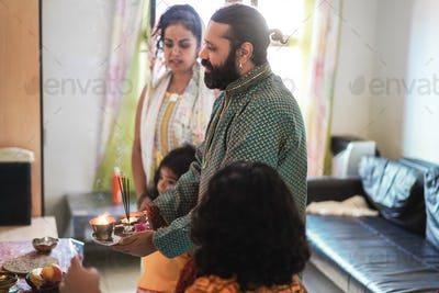 Indian family celebrating Diwali or hindu festival at home - Focus on man face