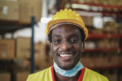 African worker man smiling on camera inside warehouse during coronavirus outbreak - Focus on mouth