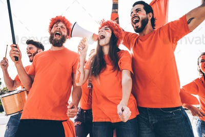 Orange sport fans screaming while supporting their team out of the stadium