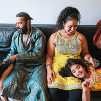 Happy indian family playing together at home sitting on sofa - Focus on woman