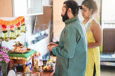 Indian husband and wife celebrating Diwali or hindu festival at home - Focus on man face
