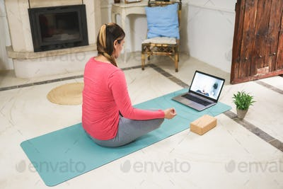 Young woman doing yoga meditation online video class at home - Focus on face