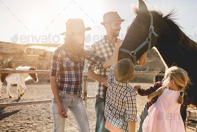 Happy family with horse having fun at farm ranch
