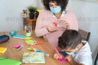 Teacher using sanitizer gel to disinfect hands with sanitizer gel - Focus on woman face