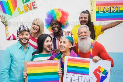 Gay people having fun pride parade with LGBT flags outdoors - Main focus on bottom guys faces
