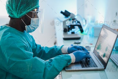 African man doctor working with laptop computer inside laboratory hospital - Focus on right hand