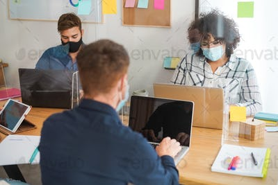 Young people working inside modern office behind plexiglas - Focus woman face