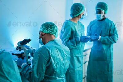 Medical workers in hazmat suit working with microscope inside modern laboratory hospital