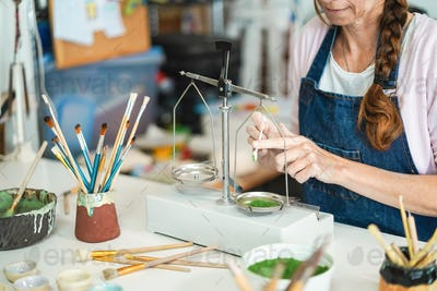 Artist woman mixing painting colors with vintage balance at pottery workshop studio -