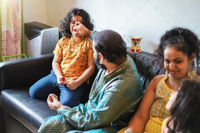 Happy indian family having fun at home sitting on sofa - Focus on mother