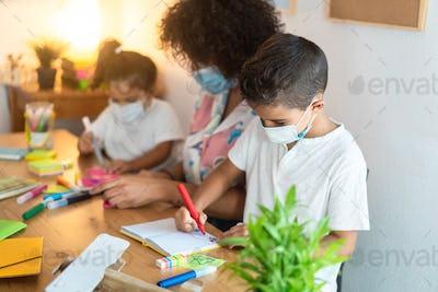 Children students painting draws with teacher inside preschool during coronavirus outbreak