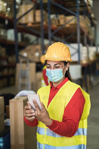 Happy worker women using mobile phone inside warehouse - Focus on face