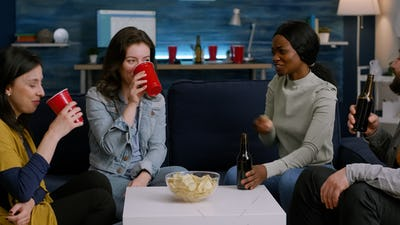 Mixed race friends cheering bottles of beer enjoying time spend together
