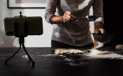 Young chef streaming virtual masterclass of cooking bakery online wat home inside kitchen