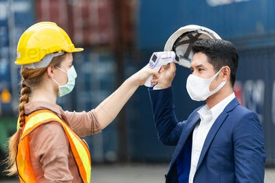 Female worker scanning fever temperature with digital thermometer at construction site