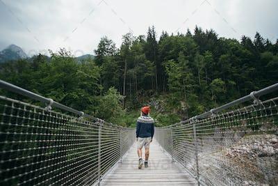 Man hiking in forest over suspension bridge