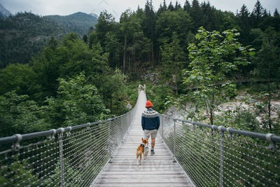 Hiker and small dog walking over suspension bridge