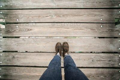 POV shot of boots on wooden boardwalk