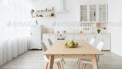 Contemporary minimalist interior of kitchen and dining room. White furniture with utensils and