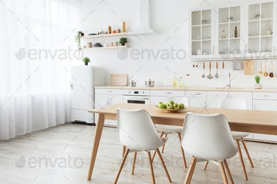 Modern kitchen interior. Wooden dining table, white chairs and furniture with utensils, empty space