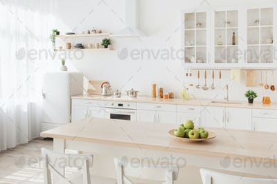 Bright kitchen interior. White furniture and shelves with utensils and plates, small refrigerator