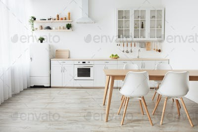 Scandinavian home interior. White kitchen furniture with utensils and dinner table with chairs