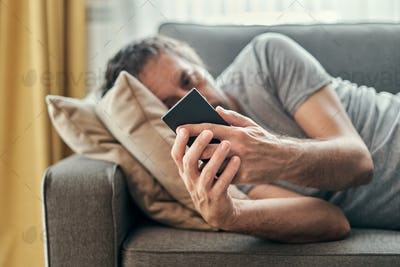 Depressed man using mobile phone while lying at living room sofa