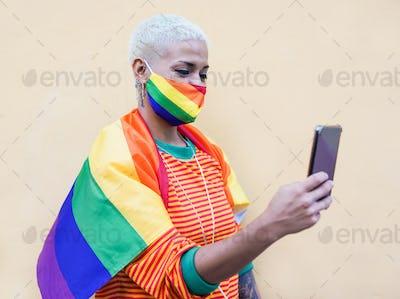 Beautiful latin woman with smartphone wearing rainbow lgbt face mask for coronavirus