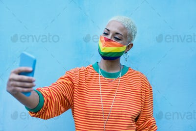 Young short hair girl with lgbt rainbow mask taking a selfie with smartphone