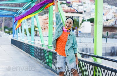 Cheerful latin woman with LGBT rainbow flag outdoor - Happy hipster girl