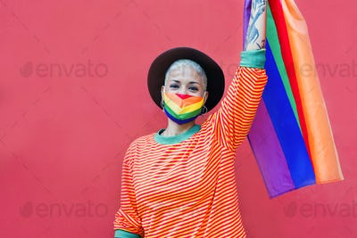 Beautiful woman with rainbow flag while wearing protective face mask - LGBT pride