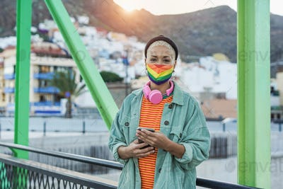 Beautiful short hair woman holing smartphone in hands while wearing lgbt rainbow face mask