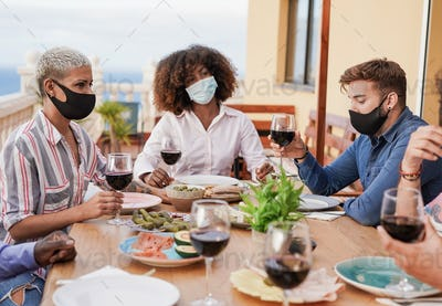Multiracial people enjoy dinner on patio at home while wearing protective face mask for coronavirus