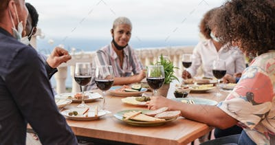Young multiracial friends enjoy dinner together outdoor