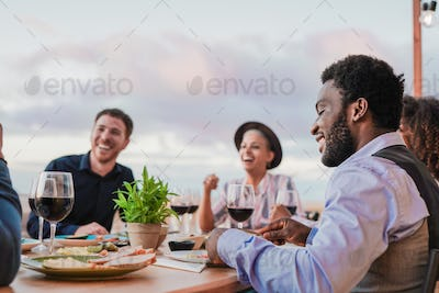 Young multiracial friends enjoy dinner together outdoor on patio - Food and drink