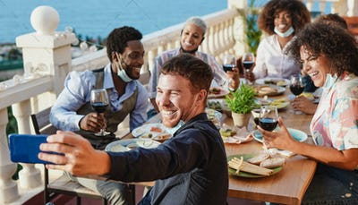 Young multiracial friends enjoy dinner outdoor on patio together and taking a selfie