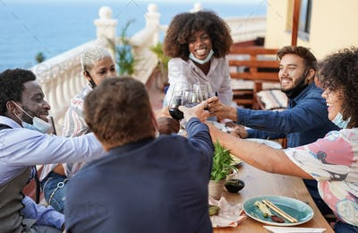 Multiracial young people celebrate outdoor on patio while wearing surgical face mask