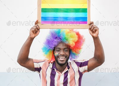 Happy gay african man with lgbt rainbow flag at gay pride event