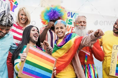 Gay multi generational people having fun at gay pride parade with banner