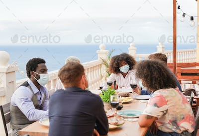 Multiracial people have a dinner outdoor while wearing protective face mask for coronavirus