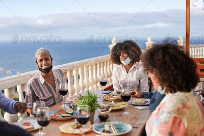 Happy multiracial friends enjoy dinner together outdoor while wearing surgical face mask under chin