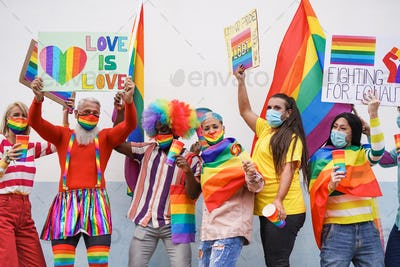 Multiracial people dance at gay pride parade with banner while wearing protective face masks