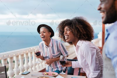 Happy multiracial people dance after a dinner outdoor on patio