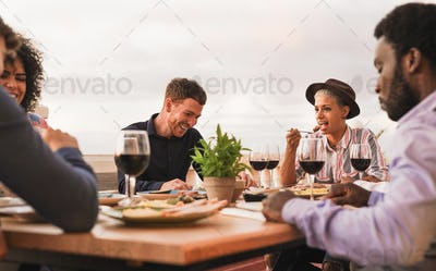 Multiracial friends enjoy dinner together outdoor on patio