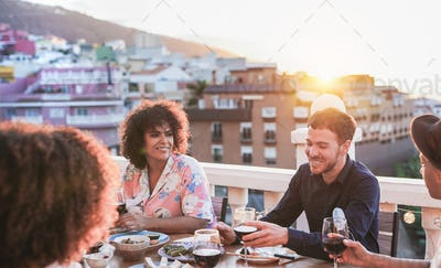 Young cheerful people enjoy dinner together outdoors home on patio at sunset