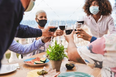 Young multiracial people cheering with red wine while wearing protective face mask