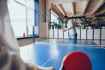 Young people, man and woman playing table tennis