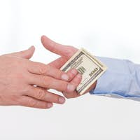 Corruption. Close-up of businessman giving money to another man while handshaking